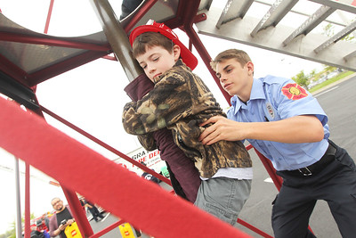 Candace H. Johnson-For Shaw Media Ethan Cade, 8, of Beach Park gets some help from Aidan Klos, of Crystal Lake, a cadet with the Wauconda Fire District, as he slides down the fire pole during the 21st Annual Fire Safety Expo at Gurnee Mills.(5/19/18)