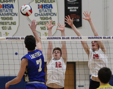 Candace H. Johnson-For Shaw Media Grant's JP Gizowski and Ian Fox attempt to block an attack by Lake Forest's Joe Chamberlain (#7) in the second set during the regional semifinal game at Warren Township High School. Lake Forest won 25-18, 25-20. (5/22/18)