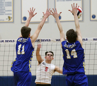 Candace H. Johnson-For Shaw Media Grant's Josh Ryczek (#5) makes an attack past a double block by Lake Forest's Kevin Lamp and Kyle Waggoner in the first set during the regional semifinal game at Warren Township High School. Lake Forest won 25-18, 25-20.(5/22/18)