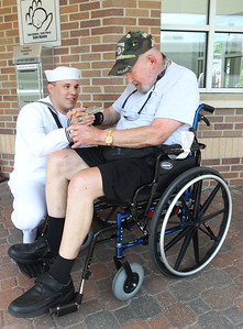 Candace H. Johnson-For Shaw Media Paul Pastrana Salgado, active Navy, Great Lakes, gives Chuck Fries, of North Chicago, a Navy veteran, an engineering challenge coin, after veterans and active duty Navy sailors from Great Lakes made their way down Main Street during the Wauconda Memorial Day Parade.(5/28/18)