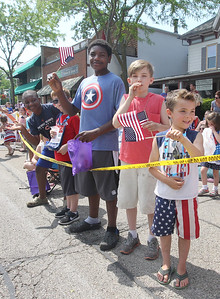 Candace H. Johnson-For Shaw Media Jesse Mork, 10, of McHenry and his brother, Sean, (center) watch the Wauconda Memorial Day Parade with T.J. Swanson, 11, of Wauconda and his brother, Toby, 6, on Main Street.(5/28/18)