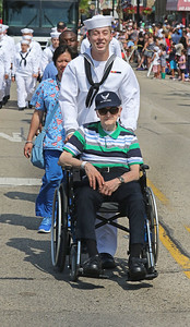 Candace H. Johnson-For Shaw Media Jean Paul Malhot, 89, of North Chicago, a WWII Air Force veteran, gets pushed in his wheelchair by Lowen Chadd, 18, active duty Navy, Great Lakes, as they make their way down Main Street during the Wauconda Memorial Day Parade.(5/28/18)