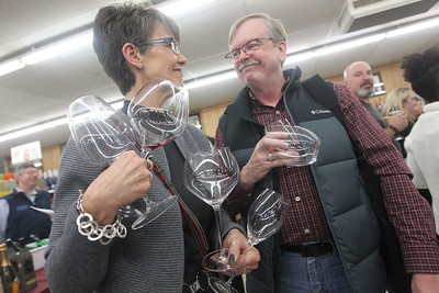 Candace H. Johnson-For Shaw Media Sandy and Neil Wyatt, of Roscoe hold on to their riedel wine glasses to try different wines during the 33rd Annual Spring Wine Tasting at Antioch Fine Wine & Liquors in Antioch. Over 120 wines were sampled at the free event. (4/27/19)