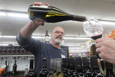 Candace H. Johnson-For Shaw Media General Manager Larry Ellis, of Trevor, Wis., pours some Ironstone red wine for a customer during the 33rd Annual Spring Wine Tasting at Antioch Fine Wine & Liquors in Antioch. Over 120 wines were sampled at the free event. (4/27/19)