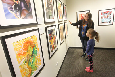 Candace H. Johnson-For Shaw Media Sarah Salto, of Grayslake, museum educator, talks with Julia Kaleta, 5, of Round Lake Beach about comic book artist, Alex Ross, as they look at his gouache paintings on display in the Marvelocity:The Art of Alex Ross exhibit during Free Comic Book Day at the Bess Bower Dunn Museum in Libertyville. (5/4/19)