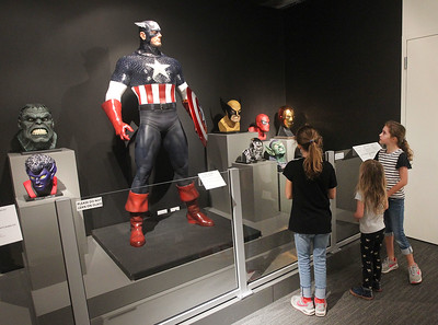 Candace H. Johnson-For Shaw Media Simone Swink, 10, of Barrington, her twin sister, Paige, and Edie Sherman, 5, of Denver, Colo., (in the middle) look at a life-size Captain America statue in the Marvelocity:The Art of Alex Ross exhibit at the Bess Bower Dunn Museum in Libertyville. Comic book artist, Alex Ross, sculpted the mask and face details of the Captain America statue.(5/4/19)
