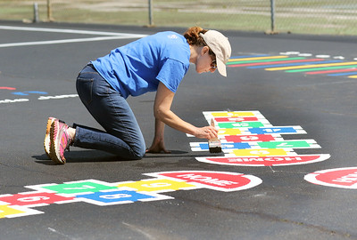 Candace H. Johnson-For Shaw Media Debbie Prather, of Antioch touches up the paint on one of the colorful hopscotch boards in the Peaceful Playground at Jensen Park created by volunteers during the NorthBridge Church's Spring ShareFest in Antioch. (5/4/19)