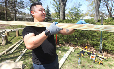 Candace H. Johnson-For Shaw Media Joshua Conde, of Antioch, first-time volunteer, carries a wooden slat as he helps to build an outdoor classroom with a team of volunteers next to the Hiram Buttrick Sawmill in Gage Brothers Park during NorthBridge Church's Spring ShareFest in Antioch. (5/4/19)