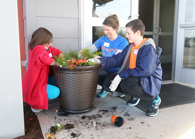Candace H. Johnson-For Shaw Media Julia Winderweedle, of Lindenhurst and her children, Kaelee, 11, and Kaedon, 13, plant shade flowers in a container outside of the entrance to NorthBridge Church during Spring ShareFest at NorthBridge Church in Antioch. (5/4/19)