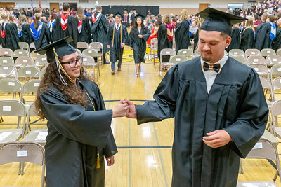 Graduates Natalia Bernal (L) and Andrew Cooke (R) shake hands during the 2019 Harvard High School Commencement ceremony Sunday, May 19, 2019 in Harvard.