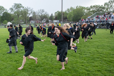 Students, faculty, and families run off the McCracken Field during the 2019 McHenry East Commencement Ceremony Wednesday, May 22, 2019 in McHenry. The ceremony was halted due to lightening in the area, and later finished inside the gymnasium at East Campus.