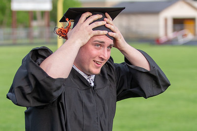 Dylan Schwartz hangs onto his cap as the wind picked up during the 2019 McHenry East Commencement Ceremony Wednesday, May 22, 2019 in McHenry.