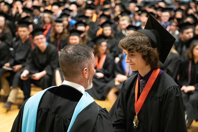 McHenry East campus principle Dr. Jeff Prickett hands Matt Venetucci his diploma Wednesday, May 22, 2019 in McHenry. The ceremony started at McCracken Field and then was moved to the East Campus Gymnasium due to lightening in the area. KKoontz – For Shaw media
