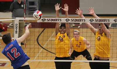 Candace H. Johnson-For Shaw Media Lakes Benjamin Mercure makes an attack against Zion-Benton's Raul Perez, Lance Storey and David Hernandez in the third set during the regional semifinal game at Antioch Community High School. Lakes won 23-25, 25-17, 25-14. (5/21/19)