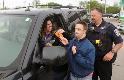 Candace H. Johnson-For Shaw Media Jennifer Steinert, of Lindenhurst makes a donation and shares a laugh with Mark Serritella, 37, of Antioch, a Special Olympics athlete, while he has a special way of giving her a coupon for a free donut with Steve Flasch, patrol officer with the Lindenhurst Police Department, beside him during Cop on a Rooftop for Special Olympics at the BP gas station and Dunkin' on Sand Lake Road in Lindenhurst. (5/17/19)