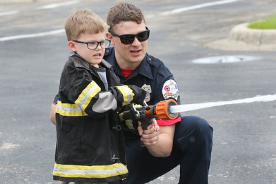 Candace H. Johnson-For Shaw Media Jackson Wnek, 5, of Volo gets some help from Jay Vance, a firefighter with the Zion Fire Department, hitting his target using a fire hose in the Kids Firefighter Challenge area during the 22nd Annual Fire Safety Expo at Gurnee Mills. (5/18/19)