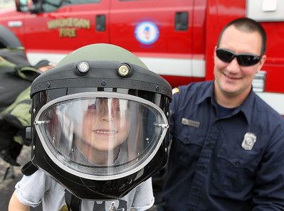 Candace H. Johnson-For Shaw Media Asher Madar, 5, of Round Lake tries on a bomb team helmet as John Calabrese, firefighter paramedic with the Waukegan Bomb Squad, watches him during the 22nd Annual Fire Safety Expo at Gurnee Mills. (5/18/19)
