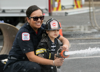 Candace H. Johnson-For Shaw Media Sarai Soto, firefighter paramedic with the Zion Fire- Rescue Department, helps Jesus Parra, 2, of Park City hit his target with a fire hose during the 22nd Annual Fire Safety Expo at Gurnee Mills. (5/18/19)