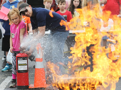 Candace H. Johnson-For Shaw Media Reagan LaManna, 6, of Wadsworth gets some help from Izaiah Guadarrama, 18, of Zion, a student at the College of Lake County Tech Campus in the firefighting program, using a modified fire extinguisher to put out a fire during the 22nd Annual Fire Safety Expo at Gurnee Mills. (5/18/19)