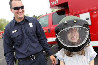 Candace H. Johnson-For Shaw Media John Calabrese, firefighter paramedic with the Waukegan Fire Department, lets Adalyn Madar, 9, of Round Lake try on a helmet used for the Bomb Squad during the 22nd Annual Fire Safety Expo at Gurnee Mills. (5/18/19)