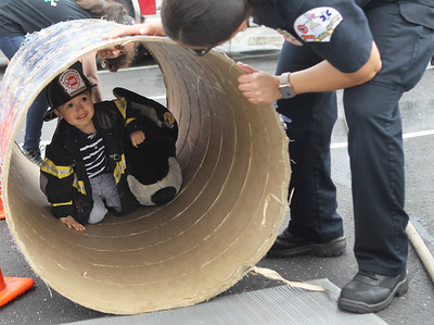 Candace H. Johnson-For Shaw Media Marisol Parra, of Park City helps her son, Jesus, 2, climb through a tunnel to see Sarai Soto, firefighter paramedic with the Zion Fire-Rescue Department, during the 22nd Annual Fire Safety Expo at Gurnee Mills. (5/18/19)