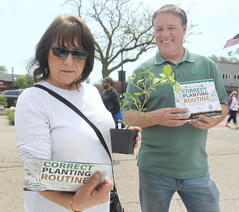 Candace H. Johnson-For Shaw Media Carol Smith, of Waukegan reads a BioGreen Organics package as she talks with Dan Neilson, of Grayslake about his company and the fertilizer he was selling during the Grayslake Greenery Garden Club Annual Plant Sale in the parking lot close to the Village Hall in Grayslake. (5/18/19)