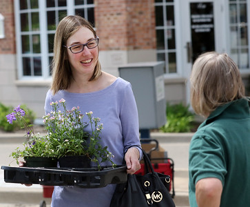 Candace H. Johnson-For Shaw Media Jennifer Mason talks with Nancy Musselman, both of Grayslake, as she answers questions for customers picking out plants during the Grayslake Greenery Garden Club Annual Plant Sale in the parking lot close to the Village Hall in Grayslake. (5/18/19)