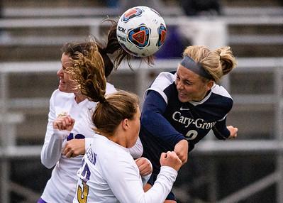 Cary Grove's Jenna Stayart heads the ball away form Hononegah's Julia Barenbaum, left, and Lydia Gleasman, center, in the second half of the preliminary game  of the 3A Guilford Sectional on Tuesday, May 21, 2019. Randy Stukenberg for Shaw Media.