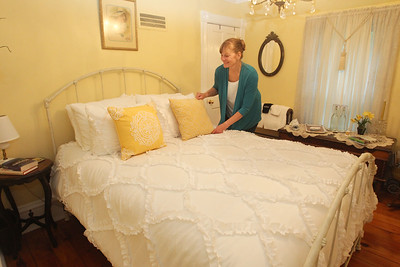 Candace H. Johnson-For Shaw Media Sheri Gronert, owner, adjusts the pillows on the queen size bed in the Daffodil Room at the Dragonfly Bed and Breakfast on Main Street in downtown Antioch. (5/28/19)