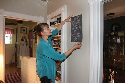 Candace H. Johnson-For Shaw Media Sheri Gronert, owner, hangs up the breakfast menu at the Dragonfly Bed and Breakfast on Main Street in downtown Antioch. (5/28/19)