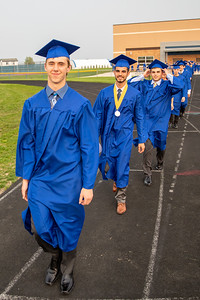 Gibson Groves (left) and other graduates walk the track and onto the field at the 2019 Johnsburg High School Commencement ceremony Friday, May 31, 2019 in Johnsburg. KKoontz – For Shaw Media