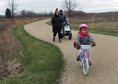 Candace H. Johnson-For Shaw Media Heather and Ryan Corah, of Gurnee take a walk with their daughters, Amelia, 1, and Maya, 5, who uses her bike to get ahead on the trail at the Rollins Savanna Forest Preserve in Grayslake. (3/31/20)