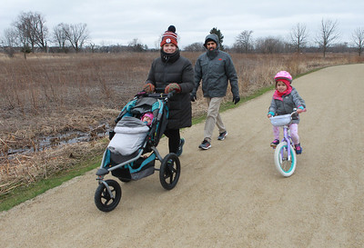 Candace H. Johnson-For Shaw Media Heather and Ryan Corah, of Gurnee take a walk and bike with their children, Amelia, 1, and Maya, 5, on the trail at the Rollins Savanna Forest Preserve in Grayslake.