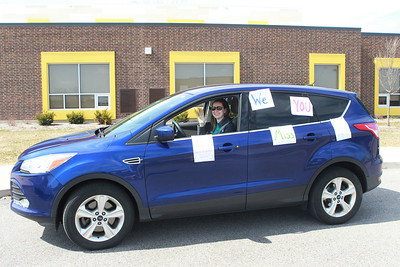Candace H. Johnson-For Shaw Media Kaitlin Pucci, of Round Lake, band teacher, sits in her car with positive messages on it as she waits to take off to tour the community waving to her students during the Petty's Staff Parade at the W.C. Petty Elementary School in Antioch. (3/25/20)