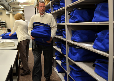 Monica Maschak - mmaschak@shawmedia.com Cheif Deputy Clerk Vern Paddock carries a precinct supply bag back to the shelf after Mary McCauley (behind) added last minute supplies.  Workers prepared election matierals to be shipped to 212 polling precincts in McHenry County.