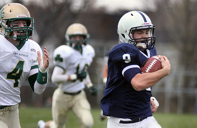 Jeff Krage – For the Northwest Herald Cary-Grove quarterback Quinn Baker is chased by St. Patrick's Mike Warner during Saturday's IHSA class 6A second-round playoff game. Cary 11/3/12
