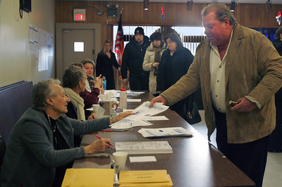 Monica Maschak - mmaschak@shawmedia.com Precinct 3 judge Bernice Diedrich hands a voter his ballot as others form a line at the American Legion Hall in McHenry yesterday.