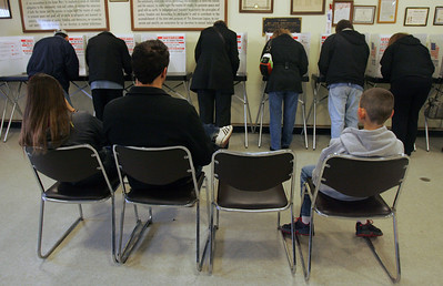 Monica Maschak - mmaschak@shawmedia.com People wait for family members to cast their vote on election day yesterday at the American Legion Hall in McHenry. Voters had the option to vote electronically or by paper ballot.