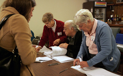 Monica Maschak - mmaschak@shawmedia.com Precinct 21 judges Terese Thompson, Len Klosowicz and Frances Larsen check for voters' names and addresses before giving them a paper ballot at the American Legion Hall in McHenry yesterday.