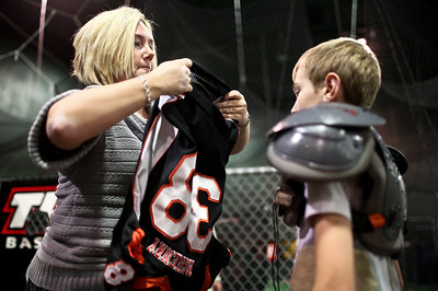 Josh Peckler - Jpeckler@shawmedia.com Gwen Rosegay of Mchenry helps put a jersey over the football pads of her son Nathan, 10 before a football practice for the McHenry Township Junior Warriors 3rd and 4th grade team at Pro Player Consultants in Mchenry  Wednesday, November 7, 2012.