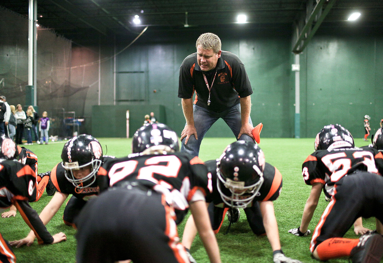 Josh Peckler - Jpeckler@shawmedia.com Joe Heinmiller facilitates a hitting drill during a football practice for the McHenry Township Junior Warriors 3rd and 4th grade team at Pro Player Consultants in Mchenry  Wednesday, November 7, 2012.