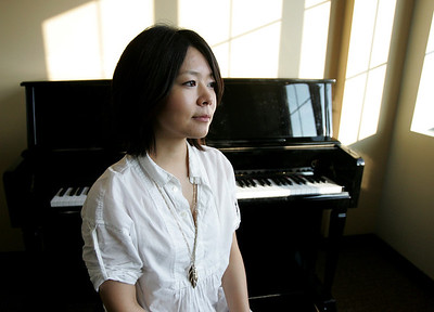 Monica Maschak - mmaschak@shawmedia.com Dr. Yokiko Fujimura, 29, of Schaumburg poses in a Cambridge Lakes piano studio in Pingree Grove on Thursday, November 8, 2012.  Fujimura is the recent artist-in-residence hire by Cambridge Lakes Charter School and will soon begin to give piano lessons to interested students in the off-campus school-owned studio.