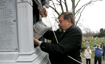 Monica Maschak - mmaschak@shawmedia.com Chairman of the Union Soldier Statue Resoration Committee Mike Czosnyka lowers a time capsule into the base of the Union Soldier Statue during a small ceremony held in the Union Cemetery in Crystal Lake on Sunday, November 11, 2012.  The time capsule contains newsletter articles and photographs about the Union Soldier Statue, a list of local men who served in the Civil War and other historical items.  A brick will soon be placed at the base of the statue stating what date the time capsule should be opened.