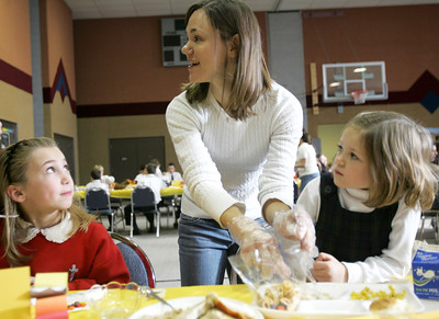 Monica Maschak - mmaschak@shawmedia.com Volunteer Kerry Balzer cuts her daughter Skyler Balzer's turkey at the annual St. John Baptist Catholic School Thanksgiving luncheon on Thursday, November 15, 2012.