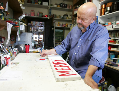 Monica Maschak - mmaschak@shawmedia.com Owner of The Woodshop Robert Novak paints a seasonal Christmas sign on old barn wood in his McHenry store Thursday, November 15, 2012.  The business, which now shares the space with Blooms & Rooms Design Studio, has been open for 42 years and the co-inhabiting businesses will be hosting winter workshops on Wednesdays and Thursdays starting on Thanksgiving.