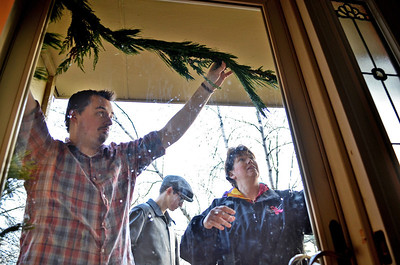 Monica Maschak - mmaschak@shawmedia.com Conor Dalton (left), 25, helps his brother, Kevin, and mother, Trish, hang a garland around the front door of their Cary home on Saturday, November 17, 2012.  Dalton moved back in with his parents and three siblings when he lost his job, got sick and when going to school in Utah got too expensive.  He is currently going to school at McHenry County College along with two of his other siblings.