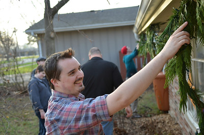 Monica Maschak - mmaschak@shawmedia.com Conor Dalton, 25, helps his brother, Ian, hang a garland on their cary home on Saturday.  The Dalton family spent the day working together to finish yard work and decorating before the weather got too cold.  Dalton moved back in with his parents after leaving Utah when school got too expensive, he lost his job and got sick.