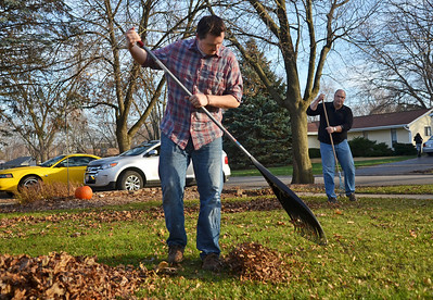 Monica Maschak - mmaschak@shawmedia.com Conor Dalton, 25, rakes leaves with his father in front of their Cary home on Saturday, November 17, 2012.  The Dalton family spent the day working together to finish yard work and decorating before the weather got too cold.  Dalton moved back in with his parents after leaving Utah when school got too expensive, he lost his job and got sick.