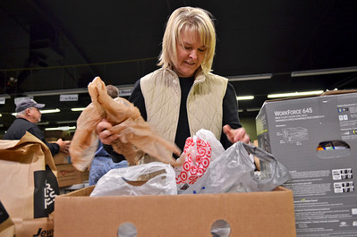 Monica Maschak - mmaschak@shawmedia.com Volunteer Audra Smith, of Fox River Grove, separates food donations into bags donated by Jewel Osco and Walmart at the Community Harvest Collection site in the Crystal Lake Plaza on Tuesday, November 20, 2012.  Donations for the food pantry will be accepted and sorted through Thanksgiving day.