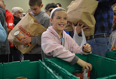 Monica Maschak - mmaschak@shawmedia.com Melissa Ivers, 10, of Crystal Lake sorts canned goods into a bin at the Community Harvest in Crystal Lake on Thanksgiving Day.